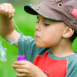 Stock Photo: Boy blowing soap bubbles