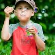 Boy blowing soap bubbles — Stock Photo