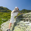 Boy climbing on mountain - Stock Photo
