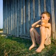 Boy sitting near wall — Stock Photo