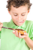 Boy spreading peanuts butter on bread — Stock Photo