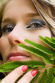 Woman with leaf over her chin — Stock Photo
