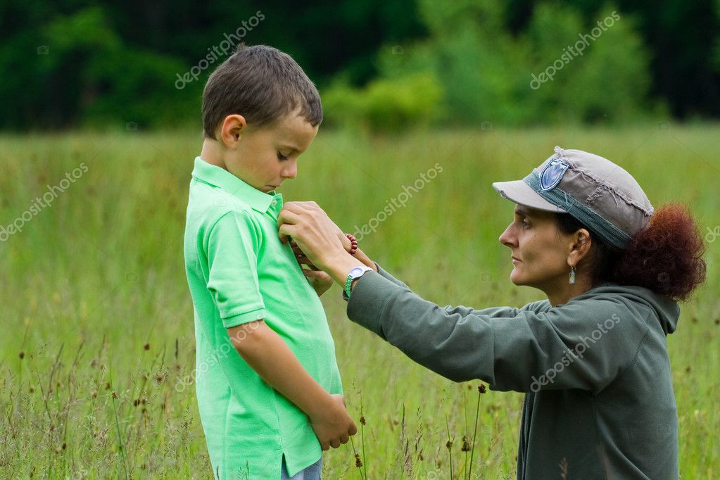 Woman helping her son get dressed, outdoor scene — Stock Photo #2254593