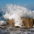Stock Photo: Wave Smashing Rocks