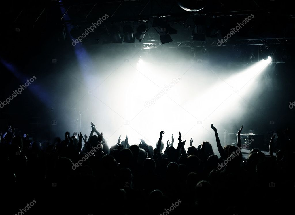 Silhouette of fans raising hands at a concert or party, bright light in the center, copy space — Photo #1954294