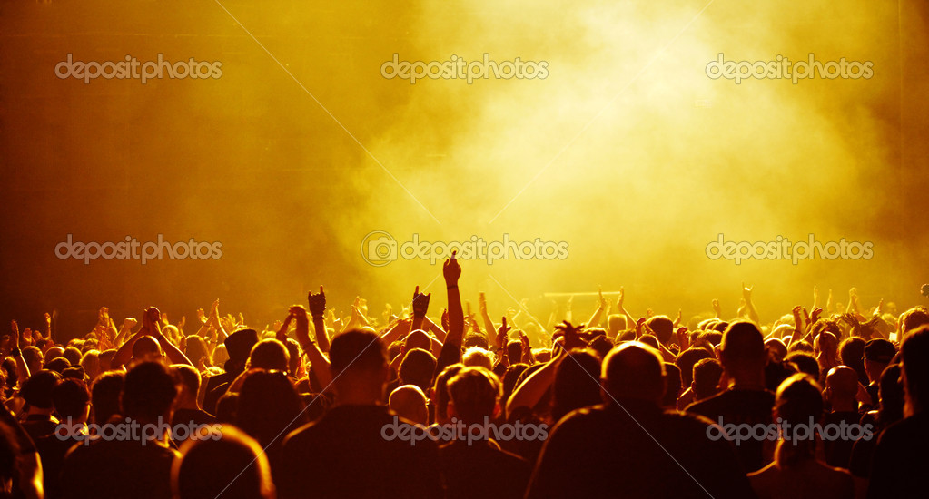 Cheering concert audience or party crowd raising hands, yellow light — Stock Photo #2087641