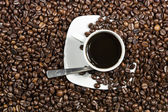 Cup with coffee on plate and beans — Stock Photo
