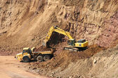 Backhoe and dumptruck at rock quarry — Stock Photo