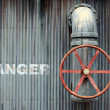 Stock Photo: Large wheel valve with danger