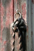 Horse rope tied to a old red barn — Stock Photo