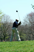 Male golfer teeing off on a ball — Stock Photo