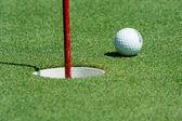 Golf ball near the cup — Stock Photo