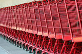 Row of red metal shopping carts — Stock Photo