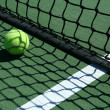 Tennis ball near net - Stock Photo