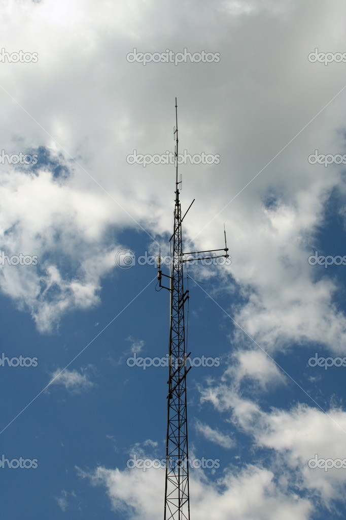 A Radio antenna against a cloudy blue sky — Stock Photo #2101909