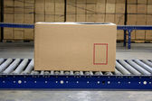 Carton on conveyor — Stock Photo
