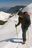Mountaineer walk on snow path on mountain with trekking pole. — Stock Photo