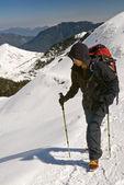 Mountaineer walk on snow path on mountain with trekking pole. — Stock Photo