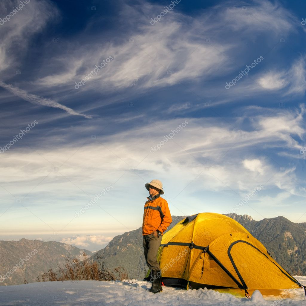 Man stand with yellow tent on snow hill against dramatic sky. — Stock Photo #2022994