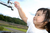 Baby wash hand and turn off faucet — Stock Photo