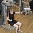 Stock Photo: Young man using an exercise machine