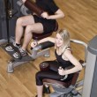 Boy and a girl using excercise machines — Stock Photo