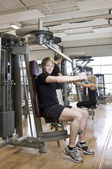 Young man using an exercise machine — Stock Photo