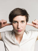 Woman with fingers in her ears — Stock Photo