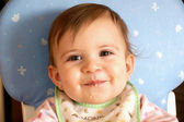 Smiling cute baby girl eating cereal — Stock Photo