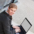 Young happy man with laptop — Stock Photo