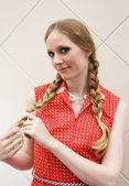 Pretty blonde girl playing with plaits — Stock Photo