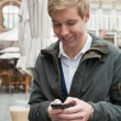 Handsome young man texting a message — Stock Photo