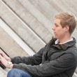 Young blond man with laptop — Stock Photo