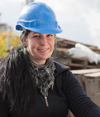 Smiling female worker in blue hard hat — Stock Photo