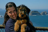 Woman holding a young airedale terrier puppy wit — Stock Photo