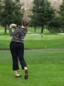 Woman golfer swinging a golf club — Stock Photo