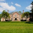 Red Brick Mansion on Green Grassy Hill - Stock Photo