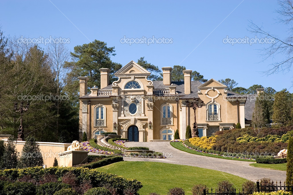 A large stucco mansion high on a manicured and landscaped lawn — Stock Photo #2061359
