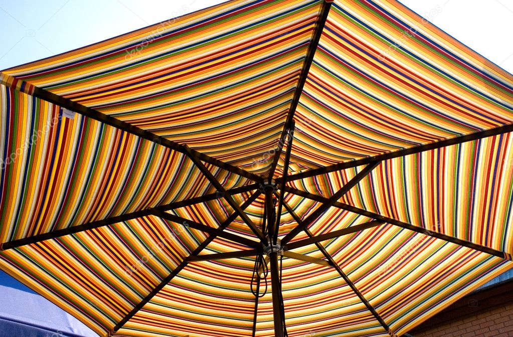 A colorful striped sun umbrella backlit by the sun — Stock Photo #2158280