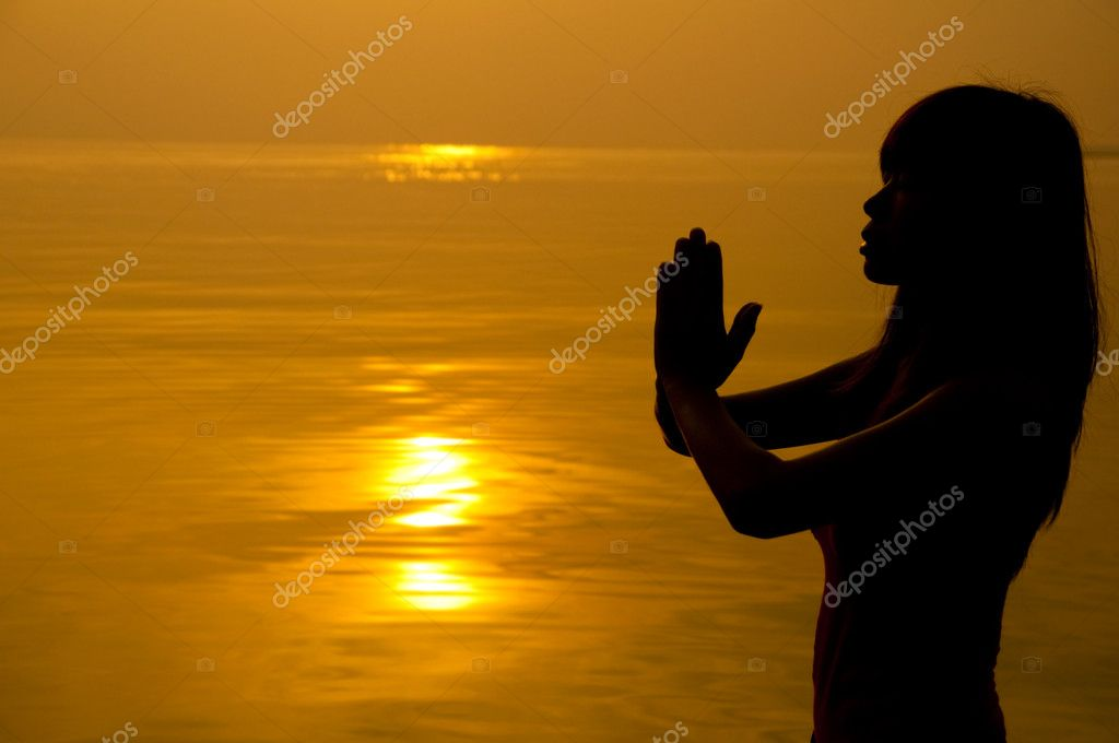 Woman with hands folded at seaside during sunset. — Stock Photo #2342580