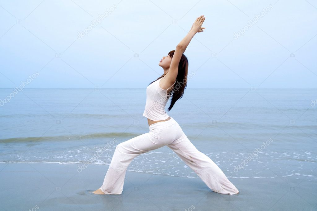 Woman practising Yoga (Warrior Position) on the beach. — Stock Photo #2345919