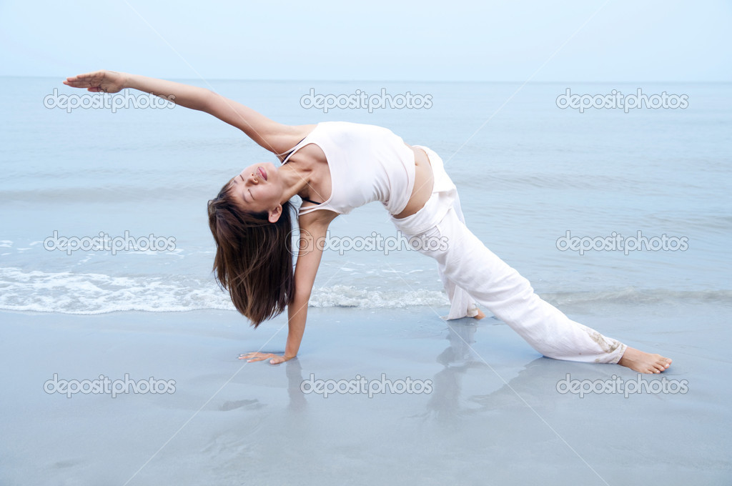 Woman practising Yoga(Gate Pose) on the beach. — Stock Photo #2346081