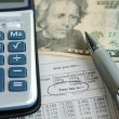 Stock Photo: Calculator on income tax table