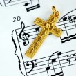 A golden cross on the music sheet - Stock Photo