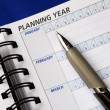 Planning the year on the day planner - Stock Photo