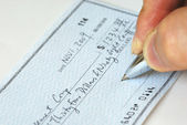 Writing a check to pay for the bill — Stok fotoğraf