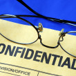 Glasses on the confidential envelope - Stock Photo