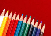 Colored pencils isolated on red — Zdjęcie stockowe