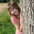 Stock Photo: Girl peers out for tree