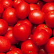 Red tomatoes by background - Stock Photo
